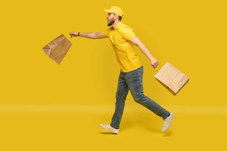Portrait of young delivery man in yellow uniform running with paper packets isolated over yellow background. Reklamní fotografie