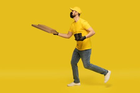 Young delivery man in yellow uniform running with pizza boxes and takeaway coffee isolated over yellow background