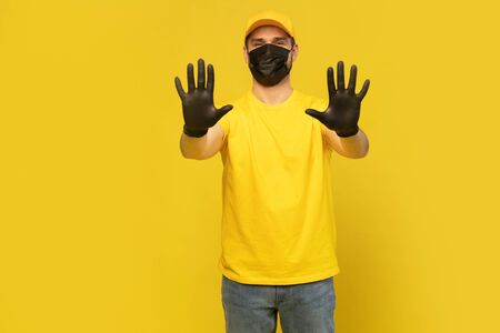 Delivery man in yellow cap, t-shirt uniform, mask gloves isolated on yellow background. Coronavirus 2019-ncov concept Фото со стока - 146386208