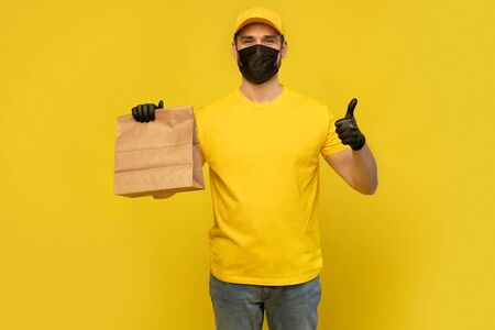 Delivery man employee in yellow cap, t-shirt, mask glove hold craft paper packet. Coronavirus virus 2019-ncov concept