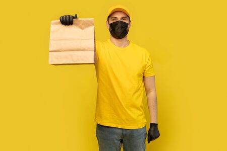 Delivery man employee in yellow cap, t-shirt, mask glove hold craft paper packet. Coronavirus virus 2019-ncov concept Фото со стока - 146386210