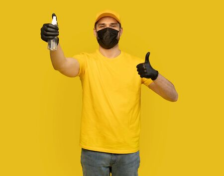 Delivery man employee in yellow uniform and mask hold bottle sanitizer soap isolated on yellow. Coronavirus 2019-ncov concept Фото со стока