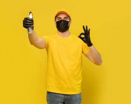 Delivery man employee in yellow uniform and mask hold bottle sanitizer soap isolated on yellow. Coronavirus 2019-ncov concept 版權商用圖片