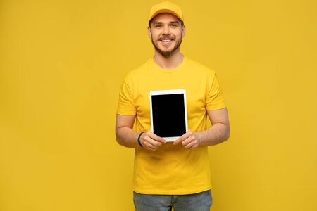 Cool delivery man with tablet. demonstrates tablet. looking at camera. isolated on yellow background. Imagens