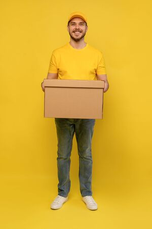 Portrait of excited delivery man in yellow uniform holding paper box isolated over yellow background.