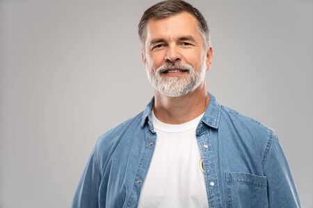 Portrait of smiling mature man standing on white background.