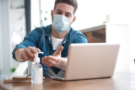 Coronavirus. Man working from home wearing protective mask. Cleaning his hands with sanitizer gel