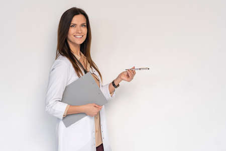 Young medical doctor woman presenting and showing copy space for product or text. Caucasian female medical professional Imagens