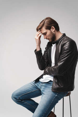 Fashion man, Handsome serious beauty male model portrait wear leather jacket, sitting on chair over white background.