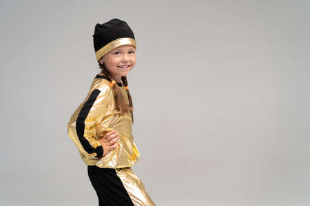 Happy little girl in gold suit dancing isolated on white background.