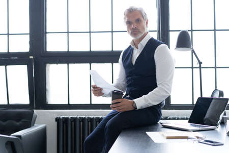 Pensive handsome matured confident businessman in trendy formal wear checking accounting report
