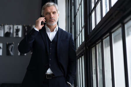 Success concept. Stylish mature bearded man in elegant suit talking on smartphone, standing near the window.