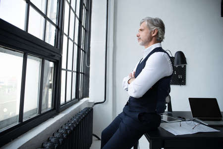 Pensive handsome matured male owner of corporation, businessman standing by his desk in office.