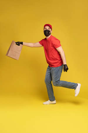 Man in red cap, t-shirt in protective mask and gloves giving fast food order isolated on yellow background. Male employee courier hold empty paper packet with food.