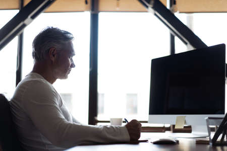 Casual Grey-haired Mature Man Working At Desk In Busy Creative Office.
