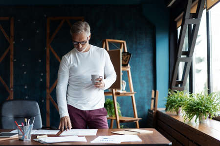 Casual Grey-haired Mature handsome architect looking at blueprint with sketch of construction in office. Stock Photo