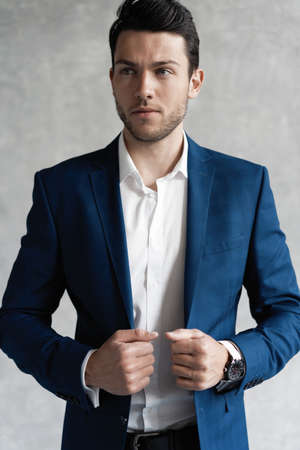 Handsome man wear blue suit isolated on grey background.