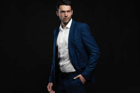 Handsome man wear blue suit isolated on black background. Reklamní fotografie