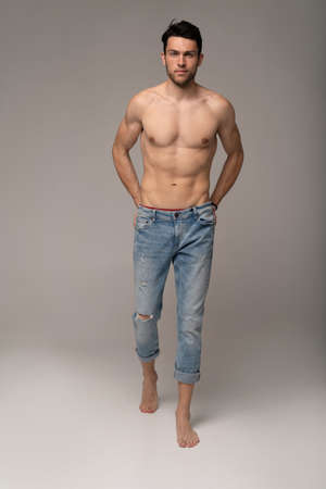 Portrait of a well built shirtless muscular male model against white background.