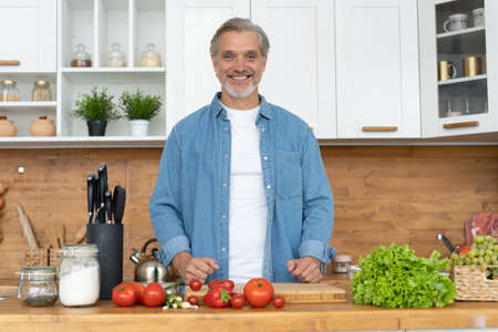 Grey-haired Mature handsome caucasian man standing in the bright kitchen