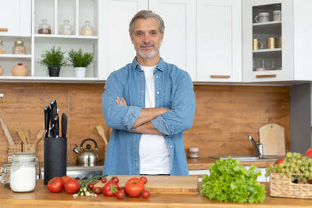 Grey-haired Mature handsome caucasian man standing in the bright kitchen 免版税图像