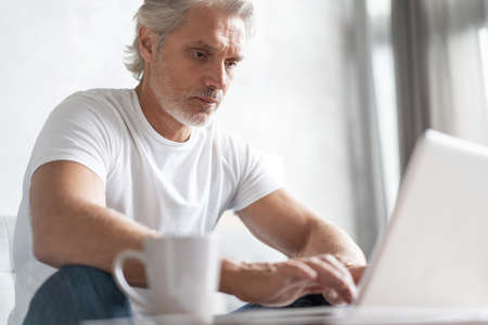 Middle-aged man working from home-office on laptop. 免版税图像