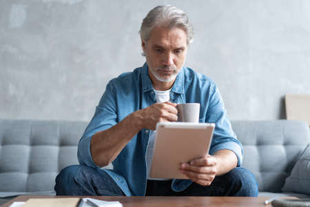 Handsome businessman working on tablet from home.