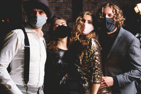 Corona virus pandemic. Group of beautiful young people in protective medical mask dancing, looking happy Archivio Fotografico