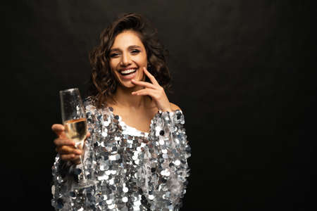 Beautiful woman wearing sparkle dress with glass of champagne on black background.
