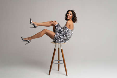 Beautiful sexy woman in sparkle dress sitting on chair on white background. 写真素材