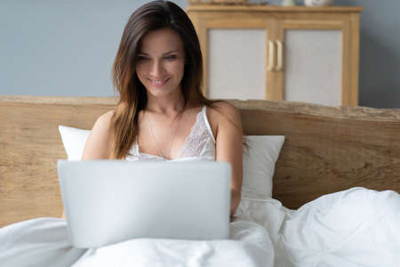 Pretty woman using her laptop in bed.