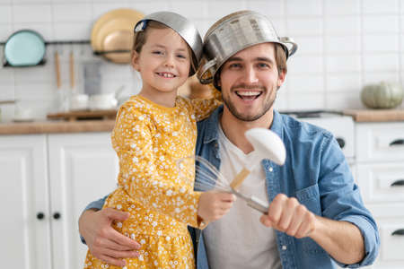 Caucasian father and daughter enjoy battle funny activity in kitchen spend active time together on weekend at home