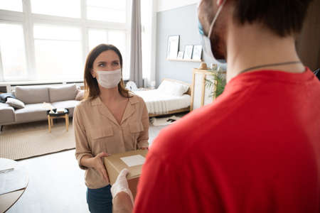 Deliveryman carry box deliver to young woman customer at home. Man wearing mask prevent virus Stock Photo