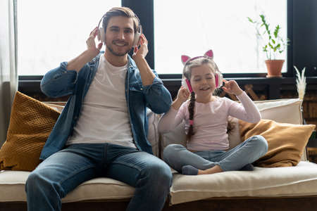 Cute little girl and her handsome father in headphones are listening to music, smiling, sitting on couch at home.