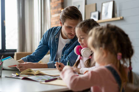 A father helping his little daughter to do her homework for the school