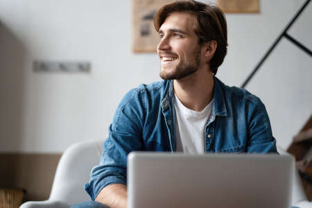 Successful entrepreneur smiling in satisfaction as he checks information on his laptop computer while working Stock Photo
