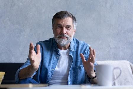 Happy senior retired man blogger looking at camera recording vlog, webcamera view portrait Reklamní fotografie