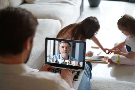Male remote working from home and having work confrence video call while daughters playing on the floor.