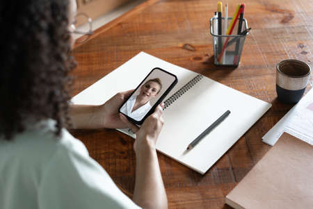 Young african american woman entrepreneur having a videocall with doctor, holding mobile phone in the office.