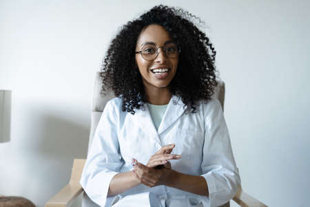 Mixed race woman doctor talking online with patient, making video call, looking at camera