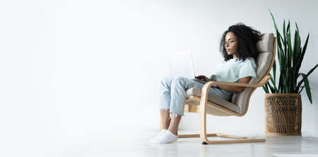 Beautiful young smiling african american woman working on laptop while sitting in bcomfortable chair at home