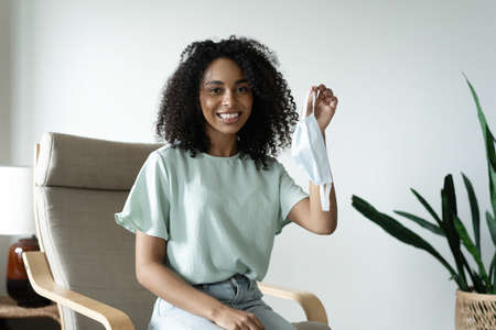 Young beautiful african american woman with curly black hair taking her medical protective mask off.