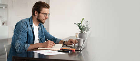 Happy young man sitting in home office and using laptop computer, smiling, chatting online