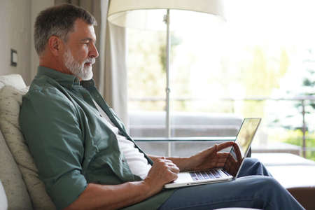 Portrait of happy mature man in casual clothes using laptop lying on sofa in house.