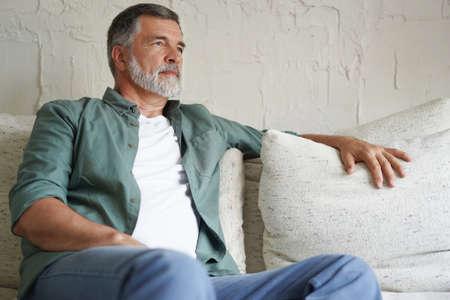 Portrait of attractive senior man sitting in sofa at home. Reklamní fotografie