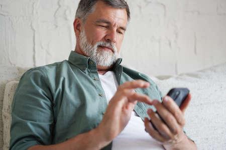 Smiling Senior Man Using Cellphone Browsing Internet Sitting On Sofa Indoor. Reklamní fotografie