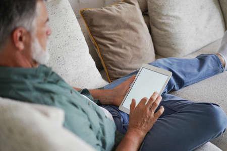 Mature handsome man websurfing on tablet at home.