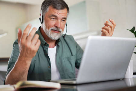 Attractive mature male remote working from home and having work confrence video call.
