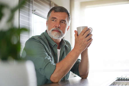 Happy mature man drinking coffee at home in the kitchen, enjoying hot drink in the morning on weekend