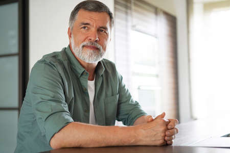 Happy attractive mature man sitting at table in kitchen.